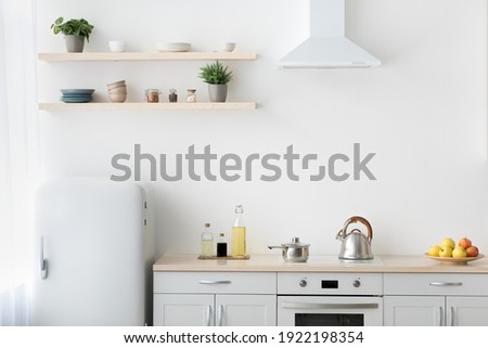 Stylish modern apartment with minimalist kitchen and Scandinavian interior. White furniture with stove, kettle and utensils. Fruits in plate, shelf with dishes and plants in pots, light wall