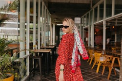 Stylish modern caucasian woman with blond hair wearing red summer dress and shawl turn around at camera