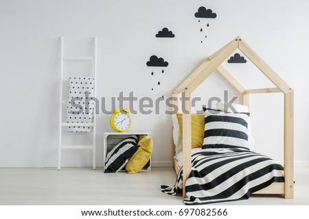 Stylish, modern child\'s bedroom with a large, yellow alarm clock, black rainy cloud stickers on the wall, and a wooden bed with striped bedding