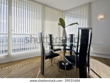 stylish modern dining room with a round glass top table and seats for five Stock photo ©