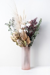 Stylish modern dried flower arrangement in a pink vase. Eucalyptus leaves, banksia, cotton flower ,gold palm, pampas grass and ruscus leaves. Art deco/Boho gift for Anniversary, birthday, mothers day.