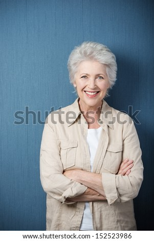 Stylish modern elderly woman standing smiling at the camera with folded arms against a green background