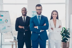 Stylish modern joyful cheerful business trio sharks in formalwear with tie, having arms crossed, standing in work place, station, looking at camera, men with bristle and glasses and beautiful woman