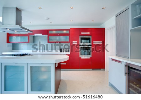 Kitchen with red cupboards and drawer and stainless steel appliances