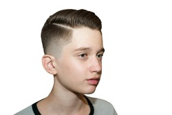 Stylish modern retro haircut side part with mid fade with parting of a schoolboy guy in a barbershop on isolated white background