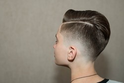 Stylish modern retro haircut side part with mid fade with parting of school boy guy in a barbershop on a brown background