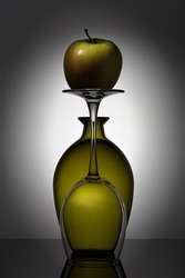 Stylish, modern still life with glass objects (a round bottle and a wine glass) and an apple.
