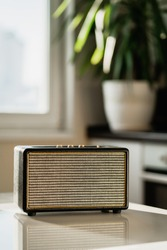 Stylish music radio channel receiver. A modern radio sits on a white table in the kitchen. Accepts the melody channel of the Wi-Fi connection. Quiet music plays.