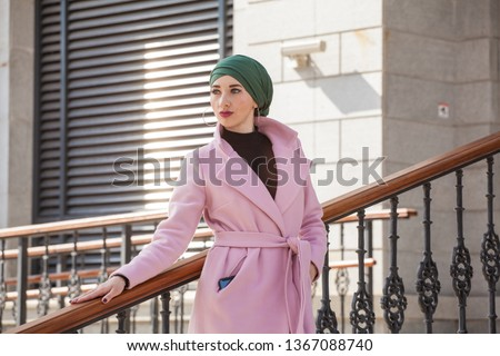 Stylish Muslim girl with a scarf on her head in a pink coat in the city. Stylish headband. The image of a modern woman in the city on the background of architecture #1367088740
