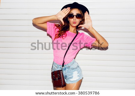 Stylish night flash fashion portrait of trendy  casual young  woman in pink neon  t-shirt , black hat, stylish shirts posing near white urban  wall along .