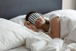 Stylish nightwear. Comfy sleeping mask helping young woman tourist traveler enjoy good healthy night sleep at new place in hotel suite room, millennial woman napping at wide king size bed in eye mask