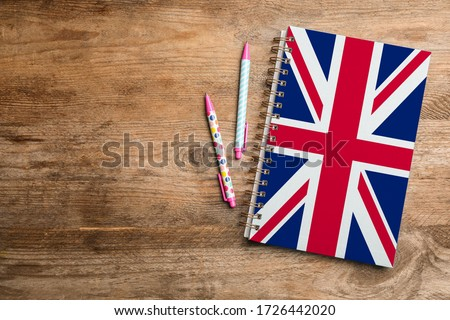 Stylish notebook and pens on wooden table, flat lay with space for text. Learning English Foto stock ©