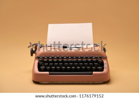 Stylish old typewriter with a paper sheet on the yellow background in the studio. Closeup. Horizontal.