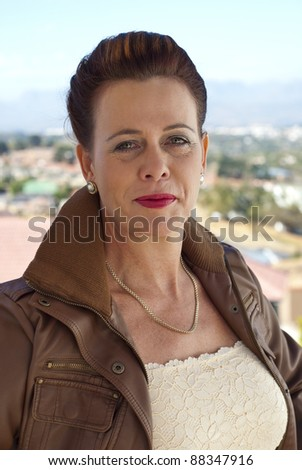 Stylish older caucasian woman in a brown leather jacket, posing casually outdoors, overlooking some houses