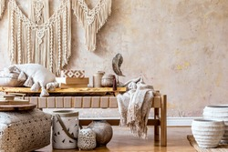 Stylish oriental living room interior with beige chaise longue, rattan decoration, pouf, pillows, shelf, wooden tray, macrame, book and elegant personal accessories in wabi sabi concept.
