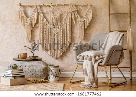 Stylish oriental living room with design armchair, beautiful macrame, big pouf, decoration, carpet, tray and elegant personal accessories in wabi sabi concept.  Foto stock ©