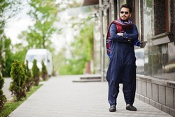 Stylish pakistani indian muslim arabic man in kurta dhoti suit and sunglasses.