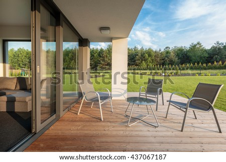 Stylish patio with wood flooring, and garden view, simple patio furniture set