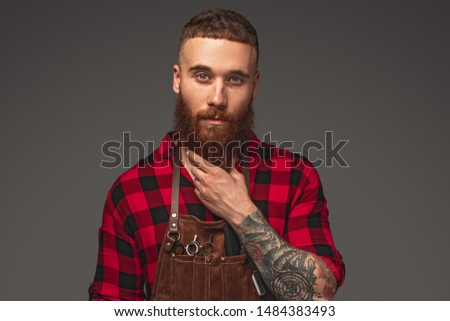 Stylish pensive barber touching beard and looking at camera while working in modern salon against gray background