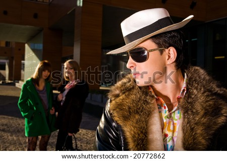 Stylish pimp in a hat and two young women on background outdoors