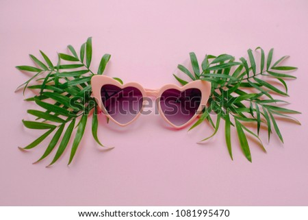 stylish pink sunglasses in heart shape and green palm leaves on pink background, flat lay. space for text. summer vacation concept. time to travel concept and relax. holidays #1081995470