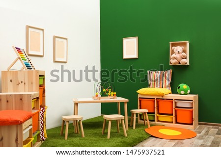 Stylish playroom interior with table and stools Foto stock ©