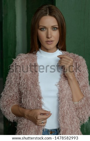 Stylish portrait fashion tall female model long brown straight hair makeup green eye woman girl in pink coat white shirt looks poses camera stay hand up hand middle background green wall