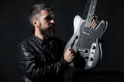 Stylish portrait of bearded men in black jacket with acoustic guitar. bearded man breaks a string on a guitar. Black background. an with long beard and mustache. Biker. Leather jacket