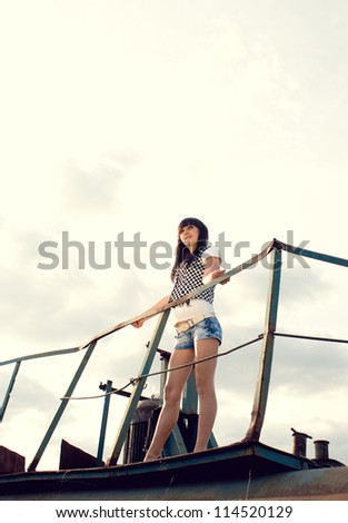 stylish portrait of young girl posing over industrial background