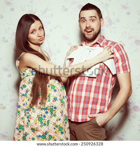 Stylish pregnancy concept: portrait of funny couple of hipsters (husband and wife) in trendy clothes (shirt, dress, jeans) holding small size baby shirt. Vintage (retro) style. Studio shot