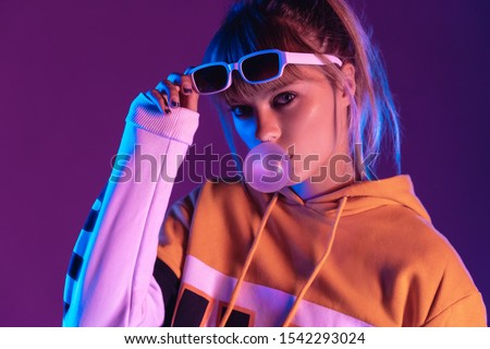 Stylish pretty young 20s fashion teen girl model wearing glasses blowing bubble gum looking at camera standing at purple studio background