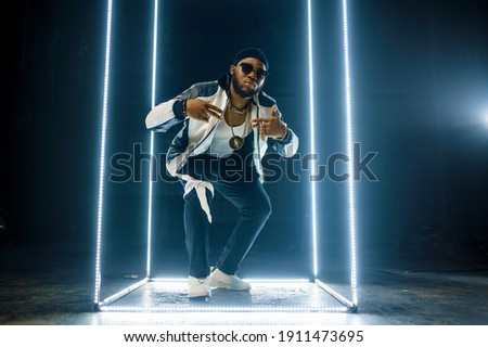 Stylish rapper in gold jewelry and sunglasses Stock fotó ©