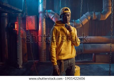 Stylish rapper in yellow hoodie and baseball cap Stock fotó ©