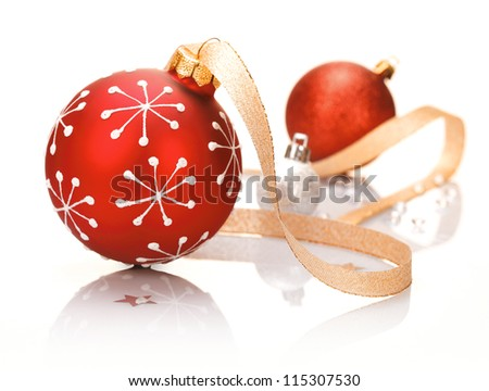 Stylish red Christmas background with a bauble patterned with snowflakes and a decorative ribbon on a reflective white studio surface