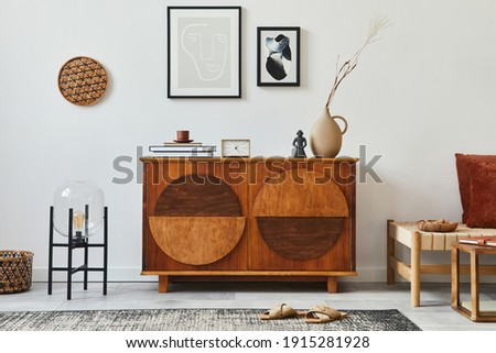 Stylish retro scandinavian living room interior with wooden commode, mock up poster frames, chiar, design stool, cacti, lamp, clock, book, decoration and personal accessories in home decor. Template.