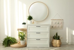 Stylish room interior with chest of drawers and round mirror