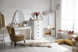 Stylish room interior with elegant dressing table, mirror and comfortable chair