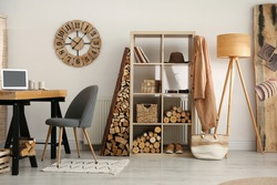 Stylish room interior with firewood as decorative element