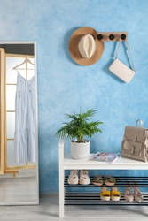 Stylish room interior with mirror, shoes and plant near light blue wall