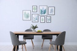 Stylish room interior with modern table, chairs and paintings of tropical leaves. Idea for design