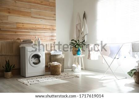 Stylish room interior with modern washing machine and drying rack