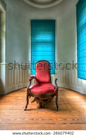Stylish room with broken old fashioned red armchair