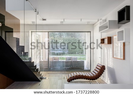 Stylish room with elegant chair, big widnow with blinds and modern stairs