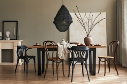 Stylish rustic interior of dining room with walnut wooden table, retro chairs, decoration, fireplace, dried flower, candlestick mock up picture frame and carpet in minimalist home decor. Template.