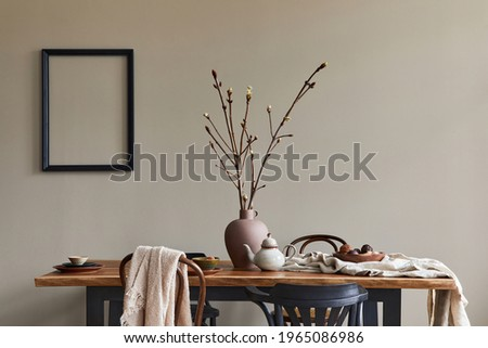 Stylish rustic interior of dining room with walnut wooden table, retro chairs, decoration, dried flower in vase and mock up picture frame in minimalist home decor. Template.