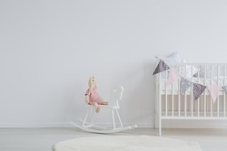 Stylish scandi design kid's bedroom with a stuffed animal rabbit sitting on a rocking horse next to a decorated baby bed