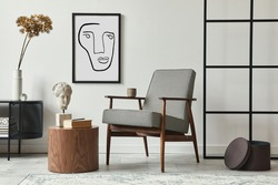 Stylish scandinavian composition of living room with design armchair, black mock up poster frame, commode, wooden stool, book, decoration, loft wall and personal accessories in modern home decor.