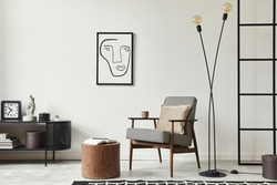 Stylish scandinavian composition of living room with design armchair, black mock up poster frame, commode, wooden stool, lamp, decoration, loft wall and personal accessories in modern home decor.