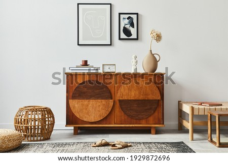 Stylish scandinavian composition of living room with design commode, black mock up poster frames, rattan pouf, clock, wooden stool, book, decoration  and personal accessories in modern home decor.
