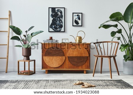 Stylish scandinavian composition of living room with design commode, black mock up poster frames, chair, wooden stool, book, decoration, plants and personal accessories in modern home decor.